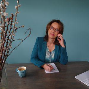 Anette de Jong van wantdatklopt.nl aan haar bureau telefonisch in gesprek