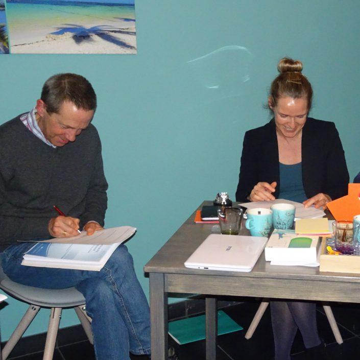 Stress training met hartcoherentie bij wantdatklopt.nl; twee deelnemers vullen geamuseerd hun werkboek in